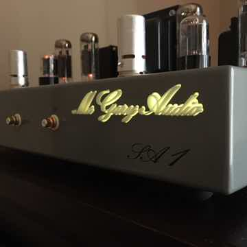 McGary Audio SA 1 Vacuum Tube Stereo Amplifier showing the backlit company logo in dark ambient lighting